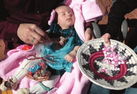 A Navajo baby during the First Laugh Party, giving gifts to family.