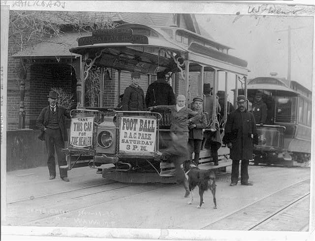 Men standing with streetcar.
