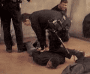 Oscar Grant is held on the ground by BART police officers.